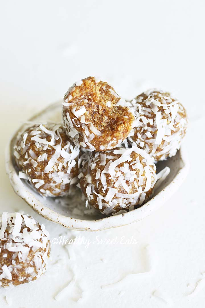 Bowl of Date Balls with a Bitten Date Ball on Top
