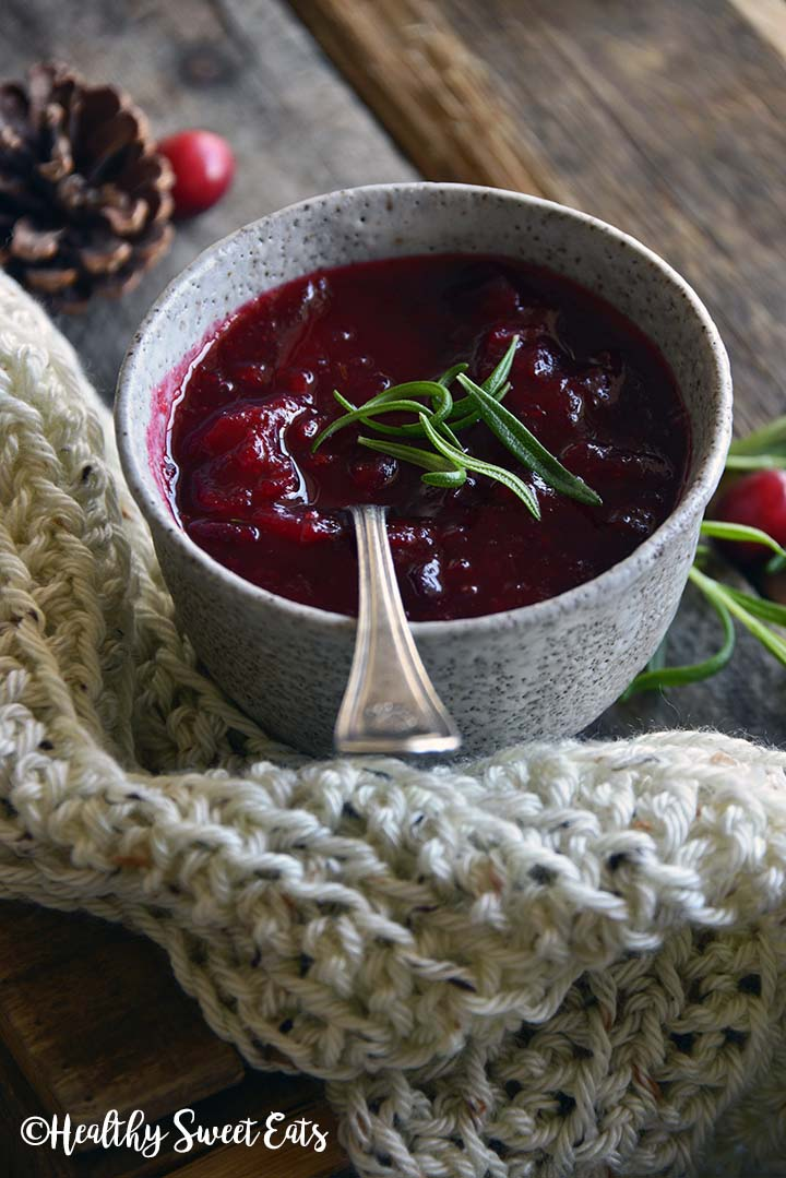 Front View of Rosemary Vanilla Cranberry Sauce (Low Carb Cranberry Sauce) with Description with Fresh Cranberries on Wooden Table