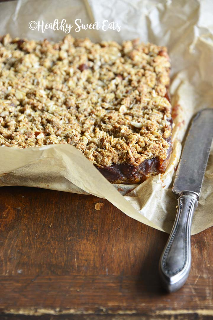 Gluten Free Almond Oat Date Crumb Bars with Vintage Knife on Parchment Paper