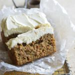 Keto Carrot Cake on Wax Paper in Wire Cooling Wrack on Wooden Cutting Board