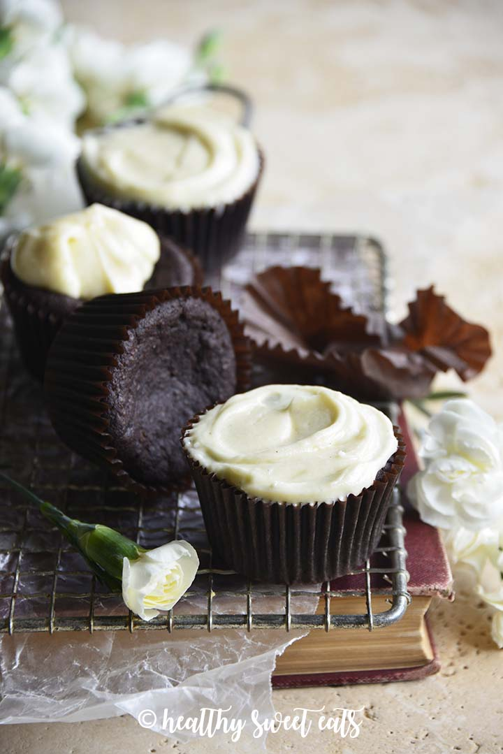 Front View of Low Carb Devil's Food Cake Cupcakes with Crème Fraiche Frosting on Cooling Rack on Top of Vintage Book