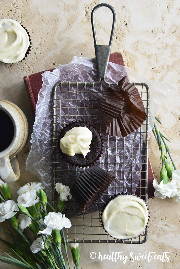 Overheat View of Low Carb Devil's Food Cake Cupcakes with Crème Fraiche Frosting on Top of Cooling Rack with Wax Paper and White Flowers