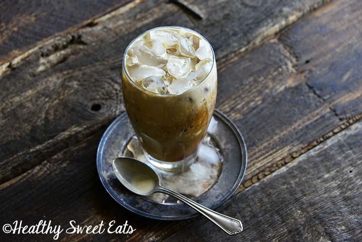 Thai Iced Tea with Vintage Spoon on Small Metal Plate on Wood Table