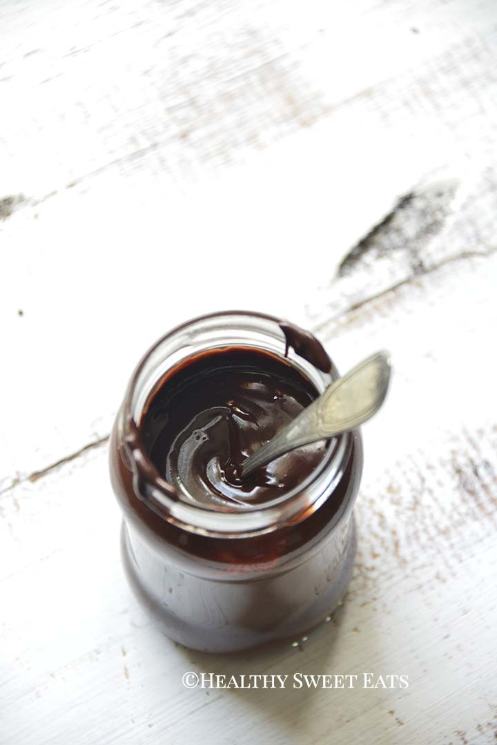 Hot Fudge Sauce in Glass Jar with Spoon on White Table